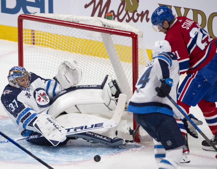 Winnipeg Jets goaltender Connor Hellebuyck (37) makes a save as Montreal Canadiens' Eric Stall and Jets' Josh Morrissey (44) look for the rebound during the second period of an NHL hockey game, Thursday, April 8, 2021 in Montreal. (Ryan Remiorz/The Canadian Press via AP)