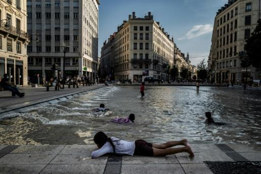 Children play in a fountain to cool off in the center of Lyon FranceMore