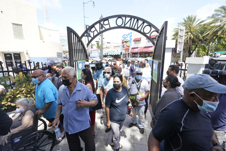 People stream into Maximo Gomez Park, also known as Domino Park, after it reopened after it was closed last year due to the COVID-19 pandemic, Monday, May 3, 2021, in the Little Havana neighborhood of Miami. (AP Photo/Wilfredo Lee)
