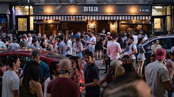 PHOTO: People drink outside a bar during the reopening phase following the coronavirus outbreak in the East Village neighborhood in New York City, June 12, 2020. (Jeenah Moon/Reuters)