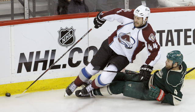 Colorado Avalanche defenseman Ryan Wilson (44) and Minnesota Wild defenseman Clayton Stoner (4) fall as they chase the puck during the third period of Game 4 of an NHL hockey first-round playoff series in St. Paul, Minn., Thursday, April 24, 2014. The Wild won 2-1. (AP Photo/Ann Heisenfelt)