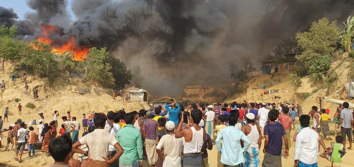 Rohingya refugees watch smoke rising following a fire at the Rohingya refugee camp in Balukhali, southern Bangladesh, Monday, March 22, 2021. The fire destroyed hundreds of shelters and left thousands homeless, officials and witnesses said. (AP Photo/ Shafiqur Rahman)