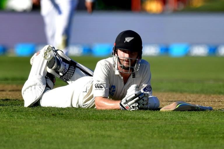 New Zealand's captain Kane Williamson lays on the ground after nearly being run out by South Africa's Kagiso Rabada on day two of their 1st Test match, at the University Oval in Dunedin, on March 9, 2017