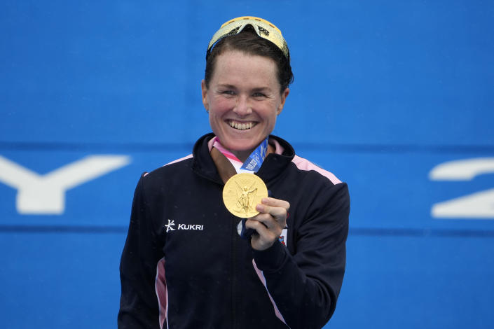 Flora Duffy of Bermuda holds her gold medal during a medal ceremony for the women's individual triathlon competition at the 2020 Summer Olympics, Tuesday, July 27, 2021, in Tokyo, Japan. (AP Photo/Charlie Riedel)