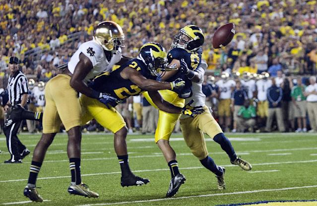 Notre Dame cornerback KeiVarae Russell (6) breaks up a pass intended for Michigan wide receiver Jeremy Gallon (21) and wide receiver Drew Dileo (9), in the second quarter of an NCAA college football game, in Ann Arbor, Mich., Saturday, Sept. 7, 2013. (AP Photo/Tony Ding)