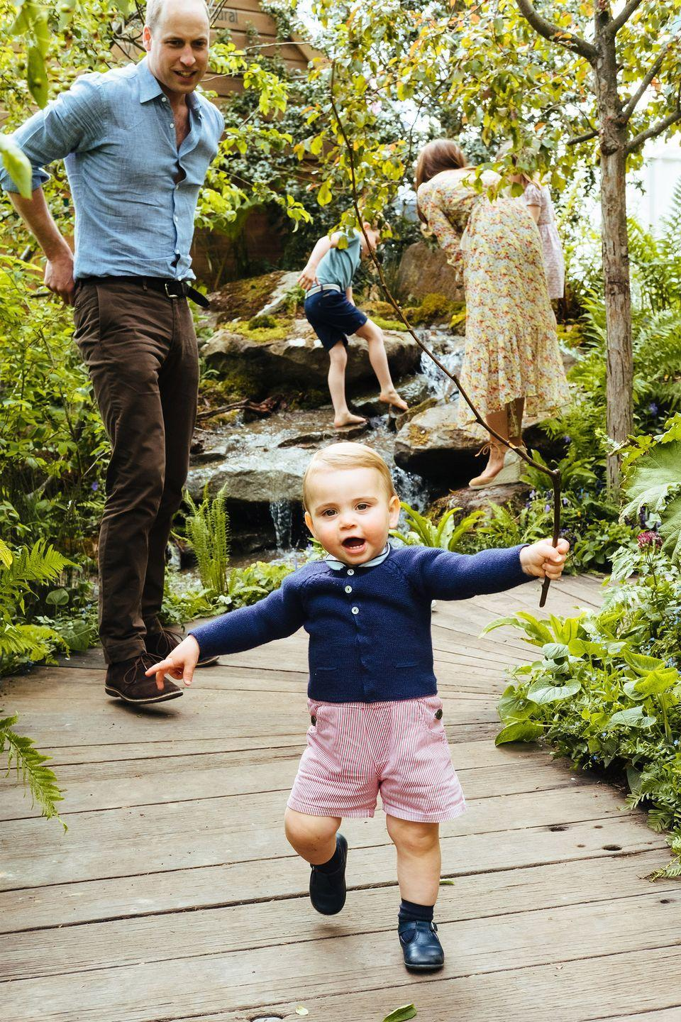 <p>That face! Prince Louis has the time of his life running around the garden with a stick he found. </p>