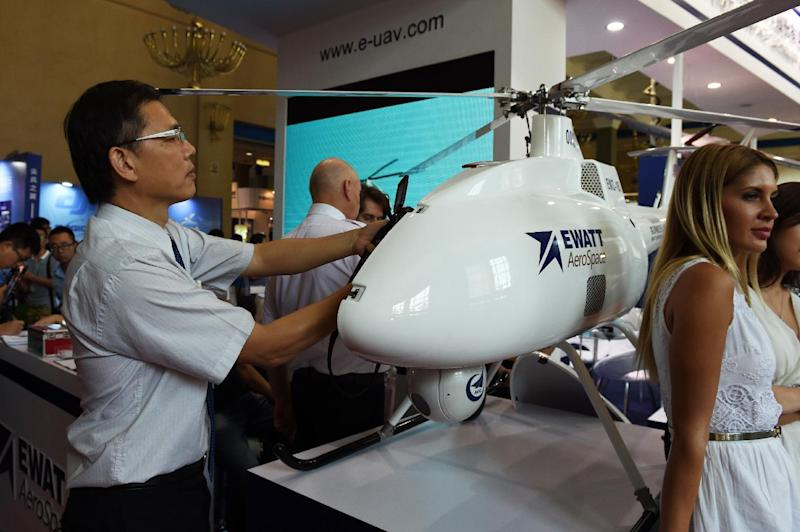 A man takes close-up photos of the inside of a drone at an exhibition of unmanned aerial vehicles in Beijing (AFP Photo/Greg Baker)