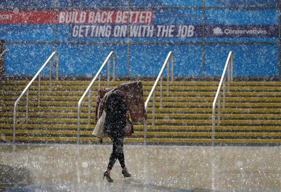 A person walks in the rain outside Manchester Central Convention Complex (Jacob King/PA) (PA Wire)