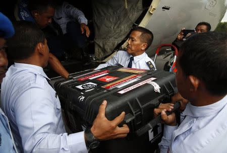 An Indonesian Air Force flight crew lift a case containing the flight data recorder from AirAsia QZ8501 onto a military plane for transport back to Jakarta at the airbase in Pangkalan Bun, Central Kalimantan January 12, 2015. REUTERS/Darren Whiteside