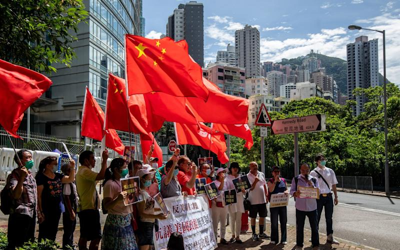 Protesters wave flags outside the Commissioner's Office of China's Foreign Ministry in Hong Kong - Bloomberg