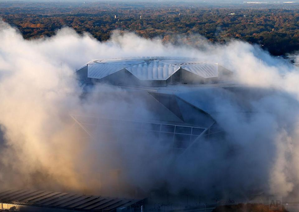 <p>A dust cloud engulfs the Mercedes-Benz Stadium following the implosion of the Georgia Dome, which was next door to the stadium in Atlanta. The Dome was the home of the Atlanta Falcons, hosted Super Bowls and the 1996 Summer Olympic Games among other sporting events. (AP Photo/John Bazemore) </p>