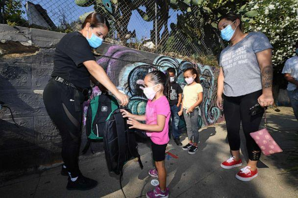 PHOTO: A volunteer hands a child a backpack filled with school supplies at a distribution to support neighborhood families, Aug. 14, 2020, in Los Angeles. (Robyn Beck/AFP via Getty Images)