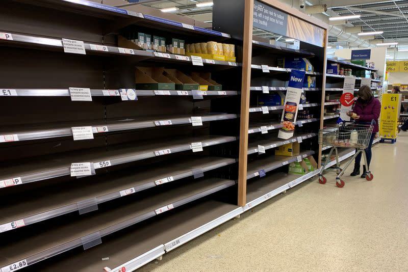 FILE PHOTO: A woman pushes her trolley along the empty pasta aisle inside a Tesco supermarket amid the coronavirus disease (COVID-19) outbreak in Manchester
