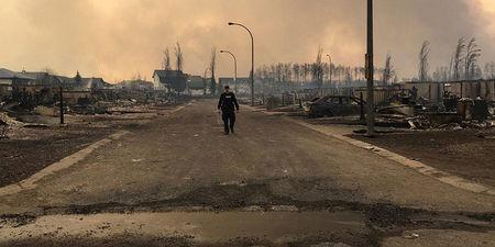 FILE PHOTO -- A Mountie surveys the damage on a street in Fort McMurray Alberta