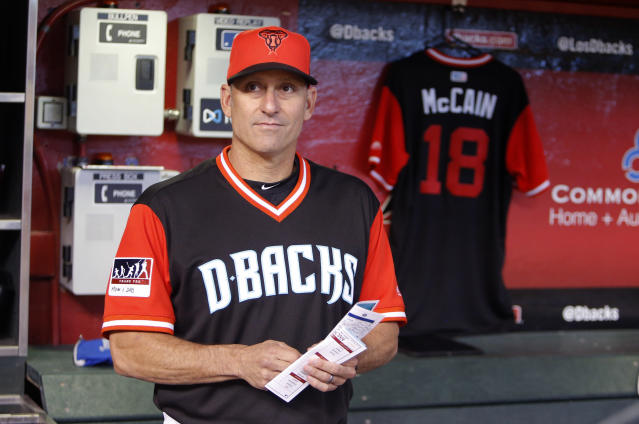 FILE - In this Aug. 26, 2018 file photo, Arizona Diamondbacks manager Torey Lovullo stands in front of a Sen. John McCain jersey in the dugout before a baseball game against the Seattle Mariners in Phoenix. With key players still on the roster and new players who should fill at least some of the void, the Diamondbacks are hoping to compete for a playoff spot even with one of baseball's best players on a new team. (AP Photo/Rick Scuteri, File)