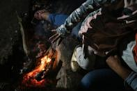 A girl from Guerrero State warms her hand over the campfire in her family's campsite in Chamizal Park in Ciudad Juarez, Mexico