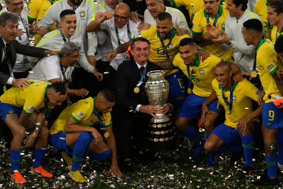 TOPSHOT - Brazilian President Jair Bolsonaro holds the Copa America trophy as members of the Brazilian national team celebrates after winning the title by defeating Peru in the final match of the football tournament at Maracana Stadium in Rio de Janeiro, Brazil, on July 7, 2019. (Photo by MAURO PIMENTEL / AFP)        (Photo credit should read MAURO PIMENTEL/AFP via Getty Images)