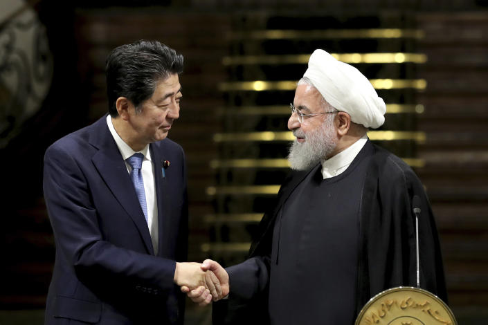 Japanese Prime Minister Shinzo Abe, left, and Iranian President Hassan Rouhani shake hands after a joint press conference at the Saadabad Palace in Tehran on June 12. (Photo: Ebrahim Noroozi/AP)