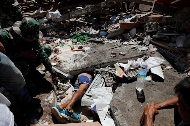 <p>A volunteer crawls beneath rubble while soldiers try to find survivors at a collapsed house after earthquake hit on Sunday in Pemenang, Lombok Island, Indonesia, Aug. 7, 2018. (Photo: Beawiharta/Reuters) </p>