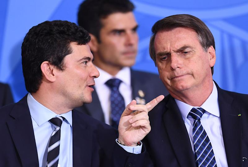 Brazilian President Jair Bolsonaro (R) and his Minister of Justice and Public Security Sergio Moro chat during the launching ceremony of the Front Brazil Project, which aims at reducing the rates of violence in cities, at Planalto Palace in Brasilia, on August 29, 2019. (Photo by EVARISTO SA / AFP) (Photo credit should read EVARISTO SA/AFP via Getty Images)