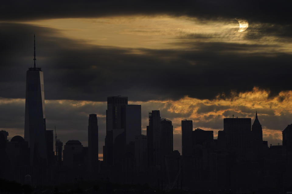 The sun is partially eclipsed as it rises over lower Manhattan in New York, Thursday, June 10, 2021. (AP Photo/Seth Wenig)