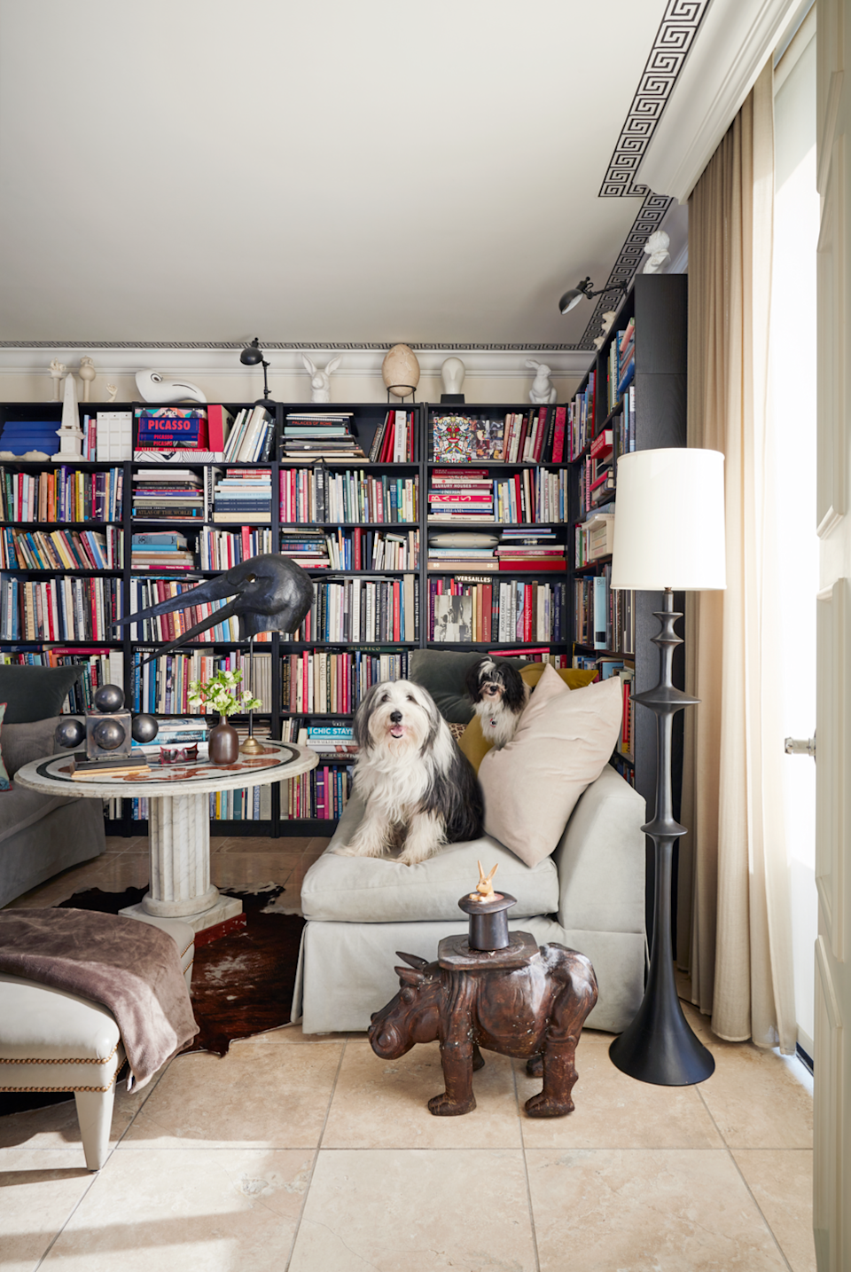 "<p>A black and beige motif is perfect for allowing an impressive (and colorful) book collection to shine, as shown here in this Atlanta home designed by <a href=""http://oetgendesign.com/"" rel=""nofollow noopener"" target=""_blank"" data-ylk=""slk:John Oetgen"" class=""link rapid-noclick-resp"">John Oetgen</a>. A Greek key border on the walls, an assortment of object, and a coffee table reminiscent of Ancient Greek architecture feels like a study for the modern Aristotle.</p>"