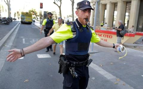 A police officer cordons off a street in Barcelona - Credit: AP Photo/Manu Fernandez