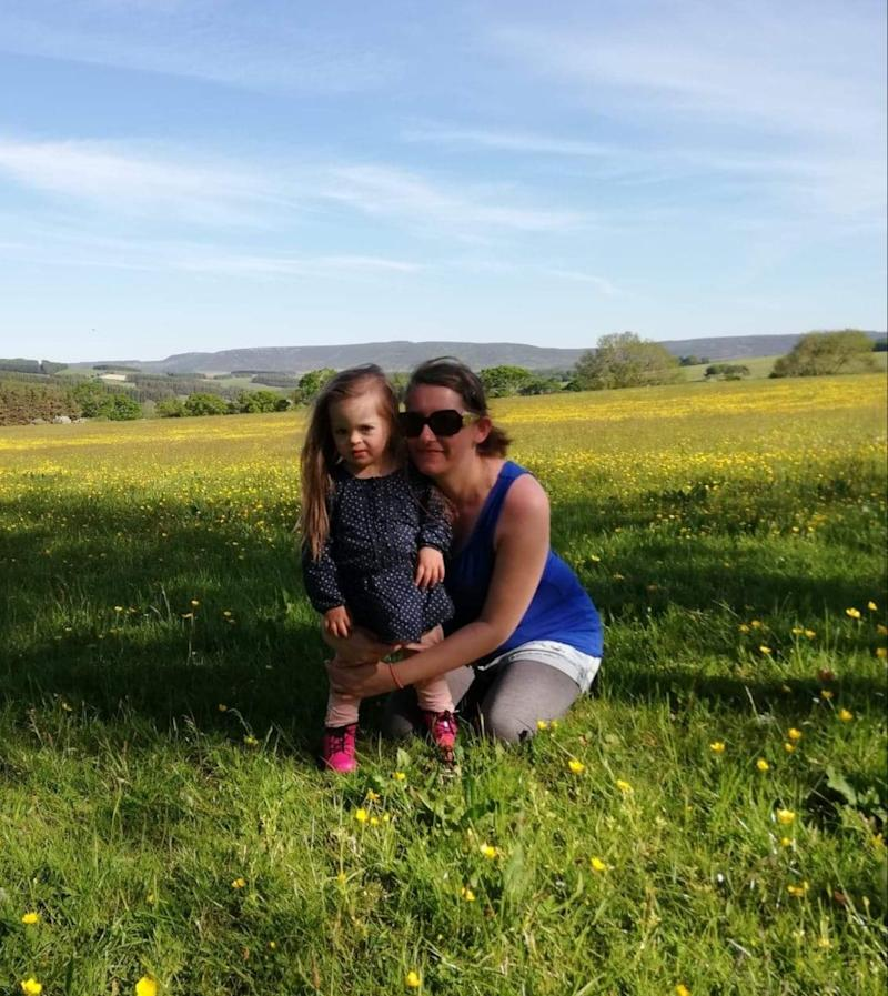 Rachel and Betsy standing in a field of grass and flowers.