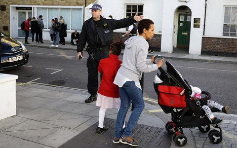 <span>A police officer direct people away from Parsons Green Tube station</span> <span>Credit: KEVIN COOMBS/Reuters </span>