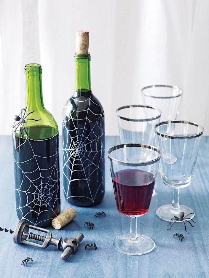 <p>Remove the labels from bottles of red wine, then take a fine-tipped white paint pen and draw on spiderwebs.</p>