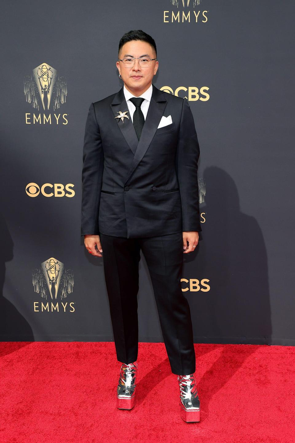 Bowen Yang wears a black suit and heels on the Emmys red carpet.