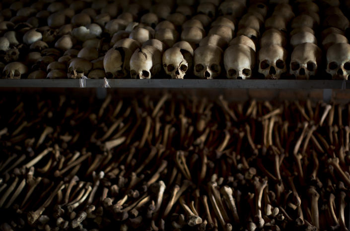 FILE - In this Friday, April 4, 2014 file photo, the skulls and bones of some of those who were slaughtered as they sought refuge inside the church, are laid out on shelves in an underground vault as a memorial to the thousands who were killed in and around the Catholic church during the 1994 genocide in Nyamata, Rwanda. France and Rwanda are hoping to reset ties scarred by a quarter century of recriminations over the 1994 Rwandan genocide when French President Emmanuel Macron visits the central African country. (AP Photo/Ben Curtis, File)