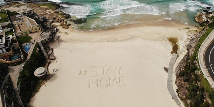 An aerial view of a notice dug into the sand reading #STAYHOME on Tamarama Beach on April 02, 2020 in Sydney, Australia.