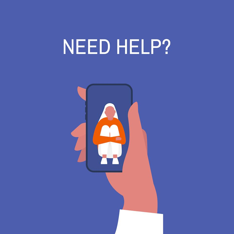 Crisis hotline. Need help? Hand holding a smartphone. New technologies. Therapy. Appointment. Mental health. Millennials. Young lonely female character hugging her knees.