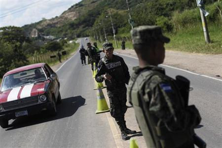 Soldiers stand at a checkpoint on a road in Tegucigalpa