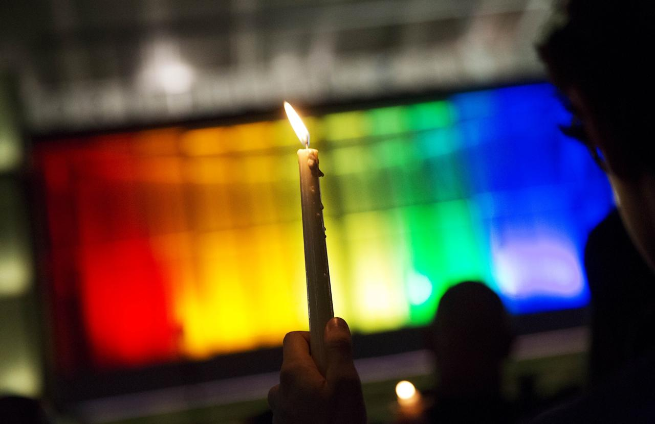 <p>A mourner holds up candle against a rainbow-lit backdrop during a vigil on Monday, June 13, 2016, for those killed in a mass shooting at the Pulse nightclub in downtown Orlando, Fla. (Photo: David Goldman/Associated Press) </p>