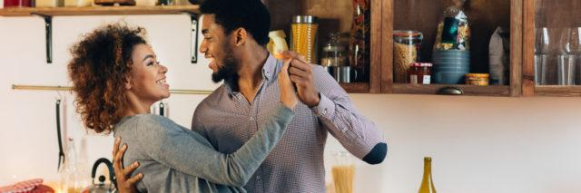 Young African-American couple dancing in kitchen