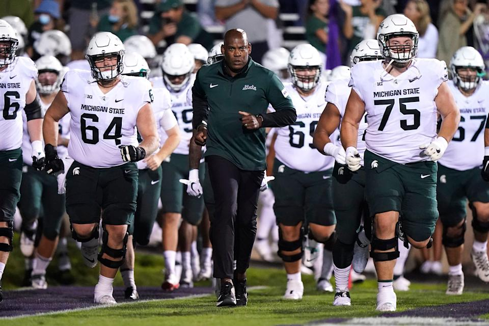 Michigan State coach Mel Tucker, center, runs onto the field flanked by right guard Kevin Jarvis (75) and center Matt Allen (64) before the Spartans' 38-21 win Friday at Northwestern.
