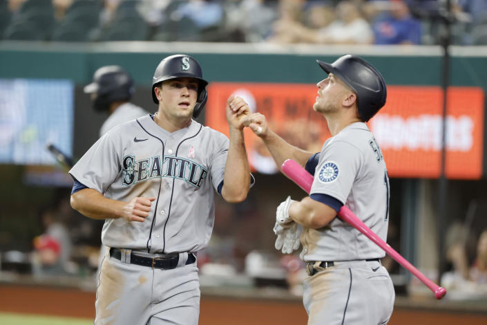 Seattle Mariners Evan White, left, is congratulated by Kyle Seager, right, after scoring a run against the Texas Rangers during the fifth inning of a baseball game Sunday, May 9, 2021, in Arlington, Texas. (AP Photo/Michael Ainsworth)
