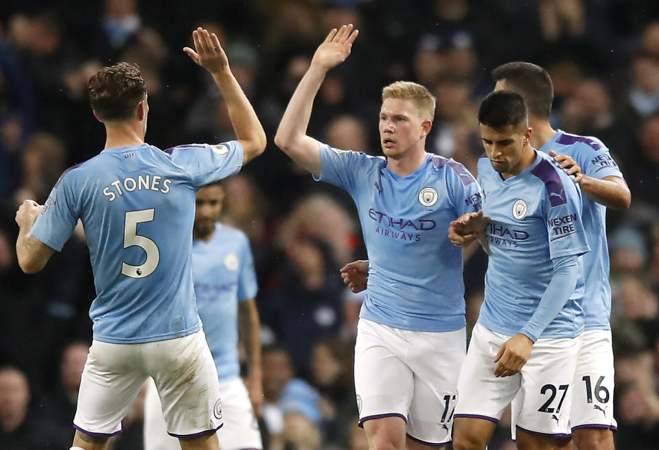 Manchester City's Kevin De Bruyne (centre) celebrates scoring his side's first goal of the game with team-mate John Stones (left) during the Premier League match at the Etihad Stadium, Manchester. (Photo by Martin Rickett/PA Images via Getty Images)