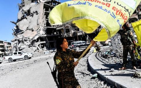 Rojda Felat, a Syrian Democratic Forces (SDF) commander, waves her group's flag at the iconic Al-Naim square in Raqqa - Credit: AFP