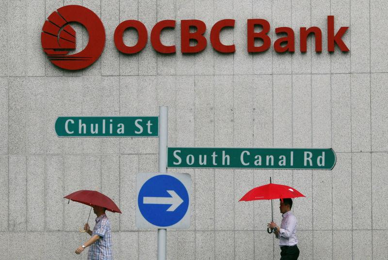 Office workers pass OCBC building in Singapore