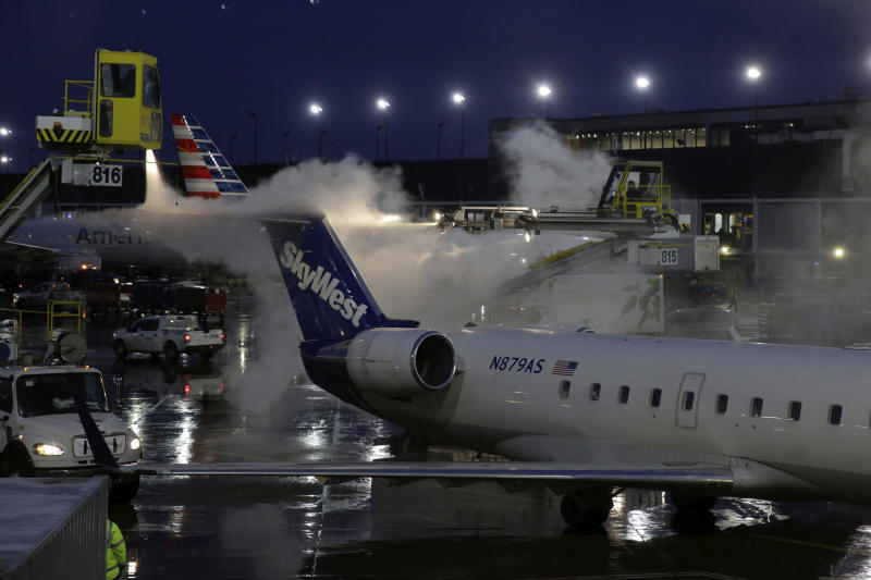 "A deicing agent is applied to a SkyWest airplane before its takeoff, Friday, Jan. 18, 2019, at O'Hare International Airport in Chicago. The National Weather Service issued winter storm warnings from the Dakotas, across the Great Lakes states and into New England. The weather service at one point warned that conditions in New England over the weekend ""could approach blizzard criteria."" Ice was also a possibility in some areas in the storm's path. (AP Photo/Kiichiro Sato)"