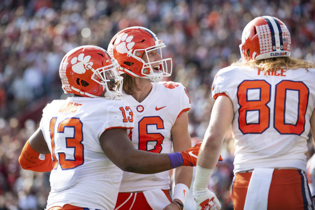 Clemson quarterback Trevor Lawrence (16), Brannon Spector (13), and Luke Price (80) celebrate a touchdown against South Carolina during the first half of an NCAA college football game Saturday, Nov. 30, 2019, in Columbia, S.C. (AP Photo/Sean Rayford)