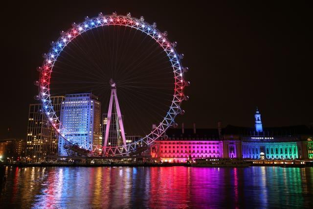 The London Eye and buildings along the South Bank are lit up with the colours of the Union flag, during a nationwide clap in honour of Captain Sir Tom Moore