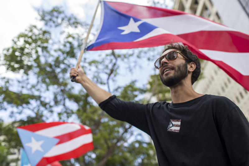 In this July 25 photo, a demonstrator flies a Puerto Rico flag as people gather to celebrate the resignation of Gov. Ricardo Rossello who announced that he is resigning Aug. 2, after weeks of protests over leaked obscene, misogynistic online chats, in San Juan, Puerto Rico. Puerto Rico's leaderless movement has drawn students, professionals, retirees, and rich and poor alike, and that's why they say it has been so successful. (AP Photo/Dennis M. Rivera Pichardo)