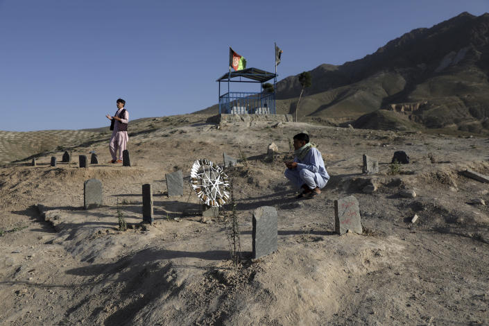 Afghan men prays near the grave of their relatives killed in bombings near Syed Al-Shahada School last month at cemetery on the outskirts of Kabul, Afghanistan, Wednesday, June 2, 2021. After the collapse of the Taliban 20 years ago, Afghanistan's ethnic Hazaras began to flourish and soon advanced in various fields, including education and sports, and moved up the ladder of success. They now fear those gains will be lost to chaos and war after the final withdrawal of American and NATO troops from Afghanistan this summer. (AP Photo/Rahmat Gul)