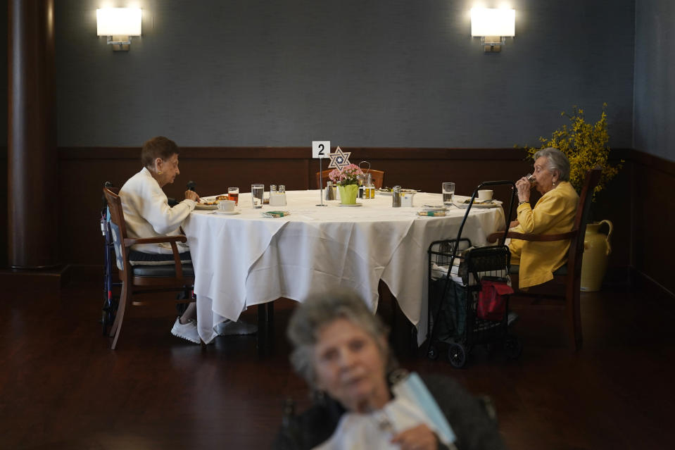 FILE - Ceil Tuder, left, and Olga Rosenson, right, eat together for one of the first times since the start of the pandemic at RiverWalk, an independent senior housing facility, Thursday, April 1, 202, in New York. Since the start of the pandemic, residents had been dining in their rooms. Only recently have they began to use the dining hall again. A focus on the elderly at the start of the nation's vaccination campaign helped protect nursing homes that were ravaged at the height of the U.S. coronavirus outbreak, but they are far from in the clear. New outbreaks, often traced to infected staff members, are still occurring in long-term care centers across the country, causing continued havoc for visitation policies. (AP Photo/Seth Wenig, File)