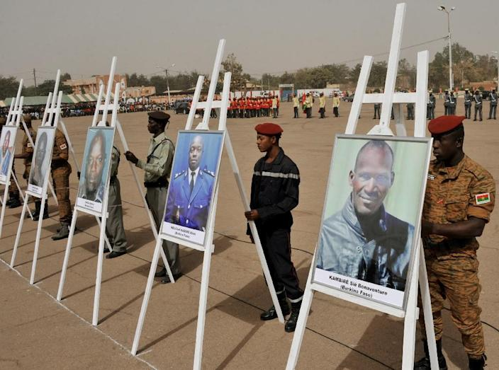 Military personnel stand behind portraits of victims during a ceremony in Ouagadougou in tribute to victims of an attack which killed 30 people claimed by Al-Qaeda in the Islamic Maghreb (AQIM) (AFP Photo/Ouoba_Ahmed )