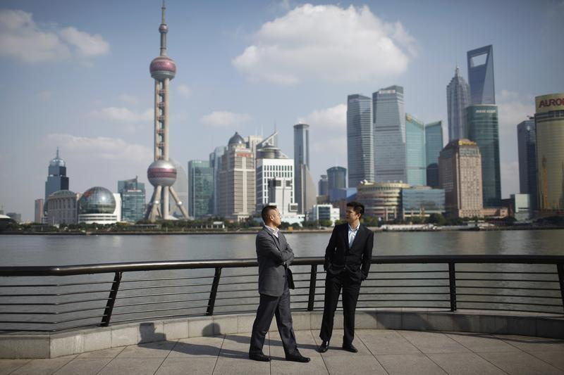 Businessmen walk on the Bund near the Huangpu River in front of the financial district of Pudong in Shanghai